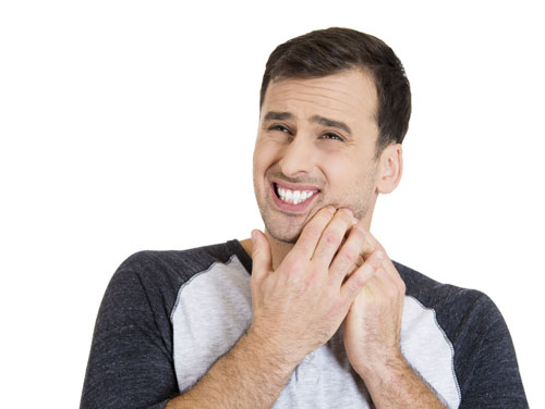 A man in pain because, he's suffering from recurring cavities.